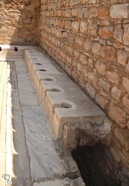 """Latrinas públicas: é possível ver o vão onde passava a água para limpeza das latrinas, bem como notar uma sutil canaleta de água aos pés do usuário, onde corria água limpa com a qual ele poderia fazer sua """"higiene"""""""